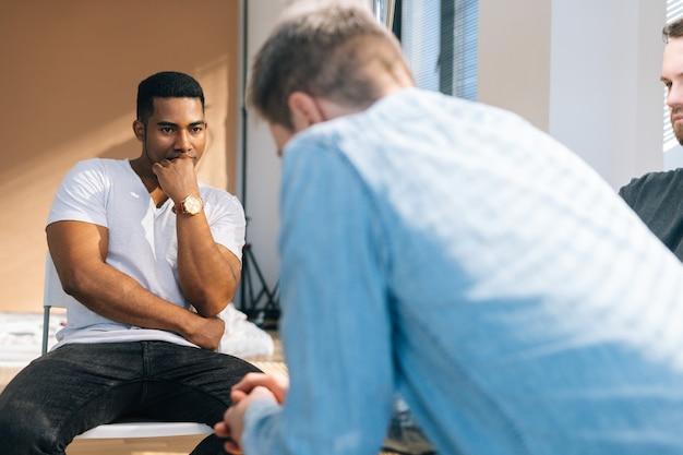 필사적으로 중독된 알코올 중독자는 대인 관계 그룹 치료 세션 동안 문제 슬픔을 공유합니다. 우울한 젊은 남성이 창문 근처의 다른 환자들에게 정신적 문제에 대해 이야기하고 있습니다.