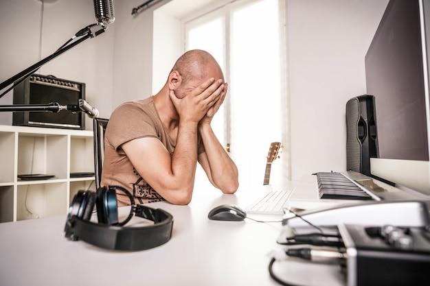 Отчаявшийся взрослый мужчина, работающий в домашней студии, когда записывающее программное обеспечение дает сбой