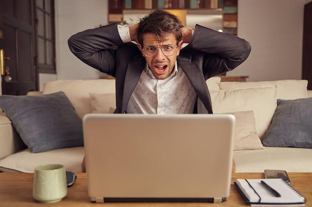 Отчаянный и сердитый молодой кавказский человек в костюме, сидя на диване перед ноутбуком. провал в бизнес-концепции. сидя дома на диване. руки на голове.