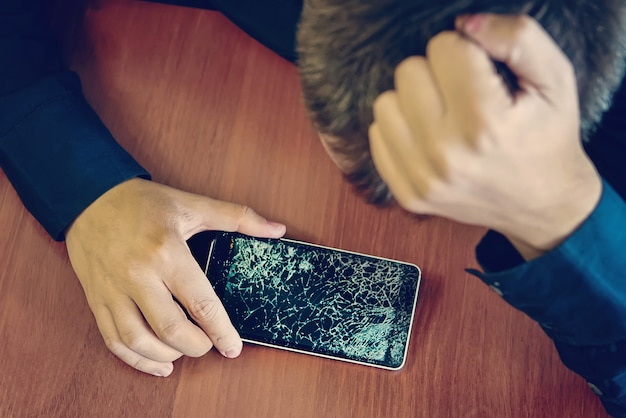 Отчаянный и удивленный мужчина держит треснувший смартфон. экран смартфона сломан. треснувший телефон сломанный телефон. грустный парень держит сломанный дорогой смартфон