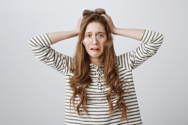パニックを起こしている曲がった眼鏡の絶望的で動揺している女性は、トラブルに巻き込まれました