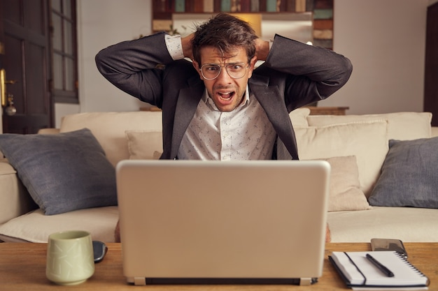 Desperate and angry young caucasian man in suit sitting on a sofa in front of a laptop. failure in business concept. sitting on the sofa at home. hands on  head.