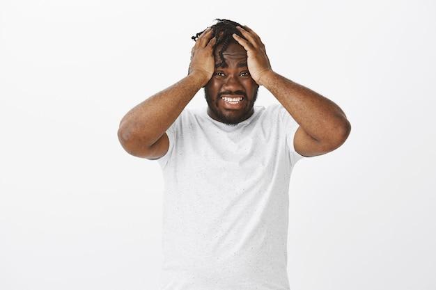 Отчаянно озабоченный парень с косами позирует у белой стены