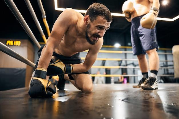 В отчаянии спортсмен стоит на коленях перед противником, опирающимся на пол правой рукой