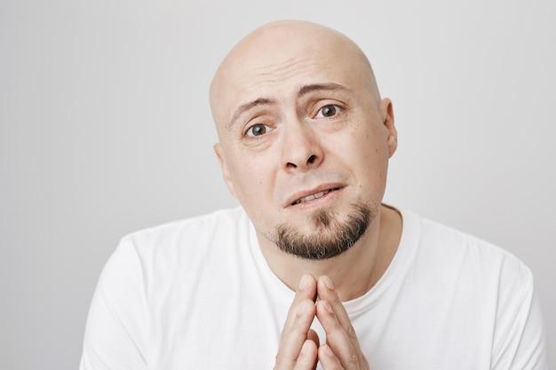 Desperate bald man pleading, asking apology