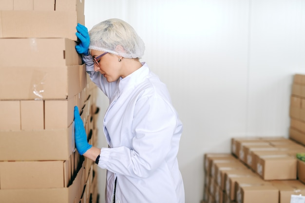 Desperate blonde female employee in sterile uniform leaning on boxes. food factory interior.
