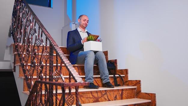 Отчаянный бизнесмен уволен, сидя на лестнице в финансовой корпоративной компании, в то время как коллеги покидают офисное здание. профессиональные успешные бизнесмены, работающие на современном финансовом рабочем месте.