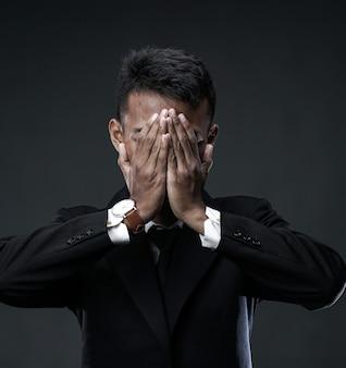 絶望的なビジネスマンの顔を覆っています。世界不況で失業