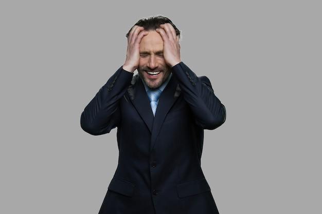 頭に手をつないで絶望的なビジネスマン。灰色の背景に欲求不満のビジネスマンを強調しました。ビジネスの失敗の概念。