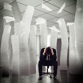 Отчаянный бизнесмен сидит среди стопок бумаг