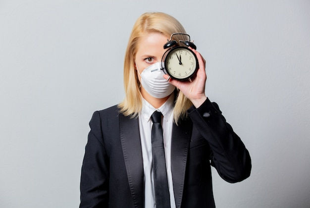 Desperate businesswoman in black suit and face mask holds alarm clock