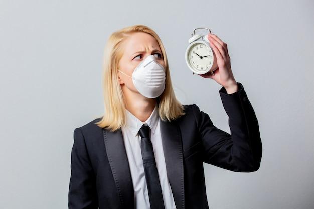 Отчаянная коммерсантка в черном костюме и маске держит будильник