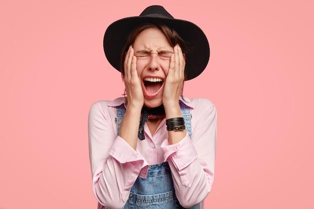 Giovane donna caucasica disperata in copricapo tiene entrambe le mani sulle guance, esclama con emozioni negative, ha problemi nel ranch