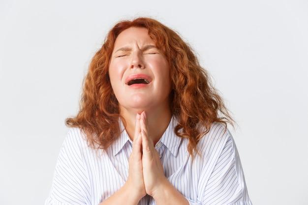 Donna di mezza età che piange disperata supplica, implorando aiuto o supplica, tenendosi per mano in preghiera, chiedendo favore, ha bisogno di qualcosa, in piedi senza speranza su sfondo bianco.