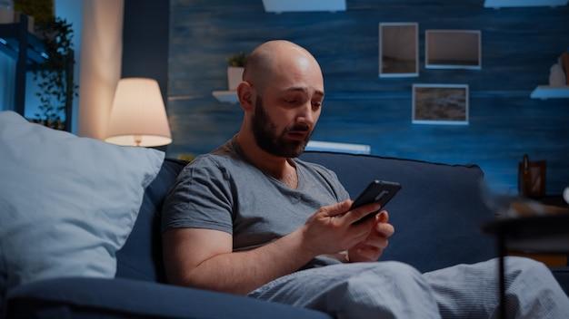 Отчаянный, подавленный, беспомощный разочарованный мужчина, читающий неоплаченные счета в цифровом банке, плачет, уведомив ...