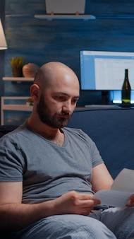 Отчаянно подавленный беспомощный разочарованный мужчина читает бумажное письмо с банковскими счетами и плачет, не имея ...