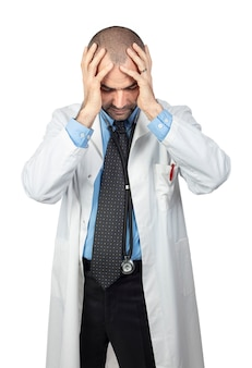 Desperate doctor holds his head in his hands, wears a white coat.