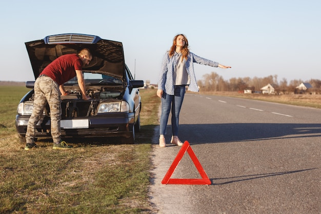 Desperate female stops vehicles on road as needs help, travel together with husband by car and have damage with engine