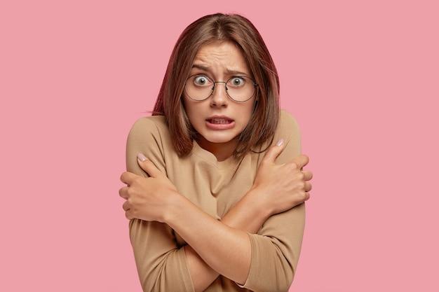 Отчаявшаяся женщина дрожит и мерзнет, обнимает себя, чтобы согреться, стучит зубами после прогулки в морозную погоду, изолирована за розовой стеной. напуганная сумасшедшая женщина замечает что-то ужасное