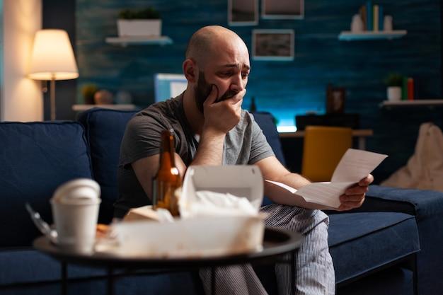 В отчаянии разочарованный напряженный молодой человек читает письмо с уведомлением об оплате долга