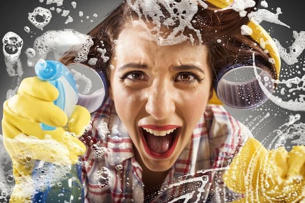 유리를 청소하는 동안 절망적 인 주부 비명