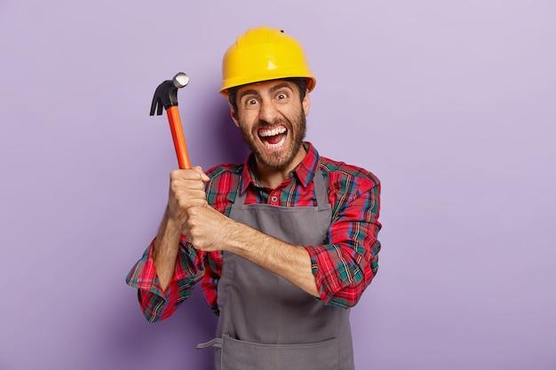 절망적 인 남성 노동자 또는 수리공은 양손으로 망치를 들고, 분노한 표정, 수리 또는 조립 준비, 보호 헬멧 착용, 건설 현장에서 일하고, 실내에 서 있습니다.