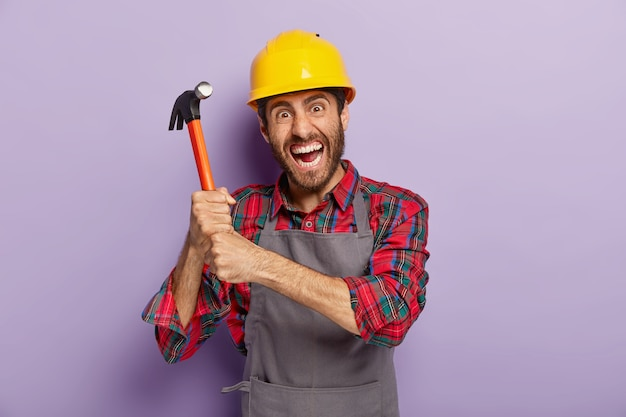 Desperate male laborer or repairman holds hammer with both hands, has outraged facial expression, ready for repairing or building, wears protective helmet, works at construction site, stands indoor.