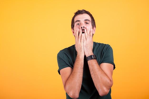 絶望的な男は、カメラを見ながら彼の顔に手を握ります。痛み、うつ病、頭痛のコンセプトイメージ