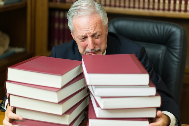 Desperate man surrounded by books