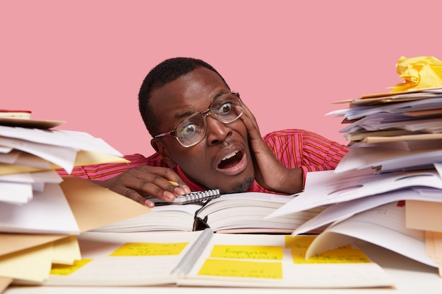 Desperate nervous dark skinned male student looks stressfully at pile of papers, writes information in notepad
