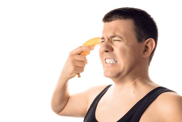 バナナを頭に向けて、必死にストレスを感じている若い男。