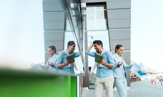 仕事で失敗する2人のビジネスマンを絶望的にします。彼らはビジネスセンターの前に屋外で立って、書類やタブレットを保持しています。