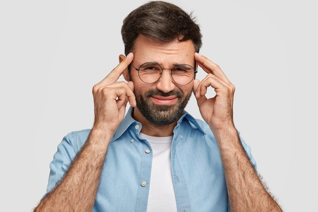 Desperate unshaven male keeps hands on temples, frowns face in displeasure, suffers from headache, dressed casually isolated over white wall. handsome man expresses frustration, negative feeling