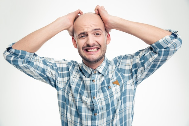 Desperate upset young man in plaid shirt with hands over head isolated on white wall