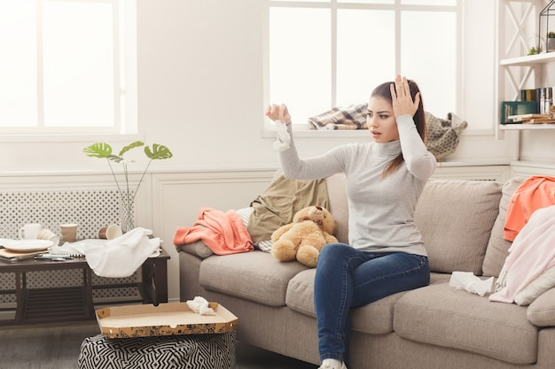 Desperate woman sitting on sofa in messy room