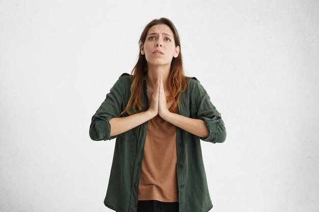 Отчаянно взволнованная молодая кавказская женщина с умоляющим взглядом, взявшись за руки в молитве, прося бога простить ее. портрет печальной несчастной женщины, сжимающей руки вместе во время молитвы