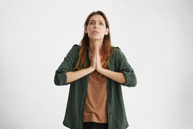 Desperate worried young caucasian female having imploring begging look, holding hands in prayer, asking god to forgive her. portrait of regretful unhappy woman pressing hands together while praying