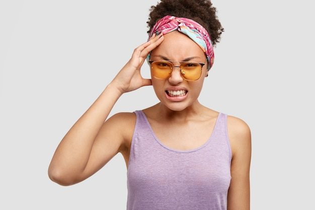 La giovane donna afroamericana disperata aggrotta le sopracciglia insoddisfatta, stringe i denti, tiene la mano sulla testa, ha mal di testa, posa contro il muro bianco. donna attraente dalla pelle scura irritata