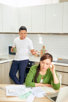Desperate young couple with many debts reviewing their bills