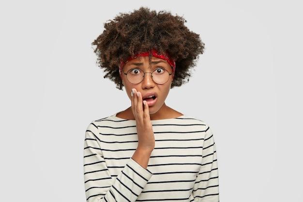 アイウェアの絶望的な若い女性は、不快に見え、開いた口の近くに手を保ち、元気がなく、白い壁に隔離された縞模様のセーターを着ています。否定的な表情の概念