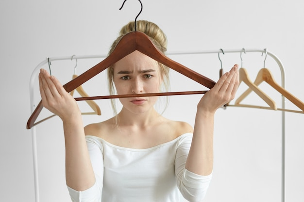 Desperate young female with hair bun having upset facial expression, looking through empty hanger, feeling frustrated, doesn't have clothes or money to buy new dress for special occasion