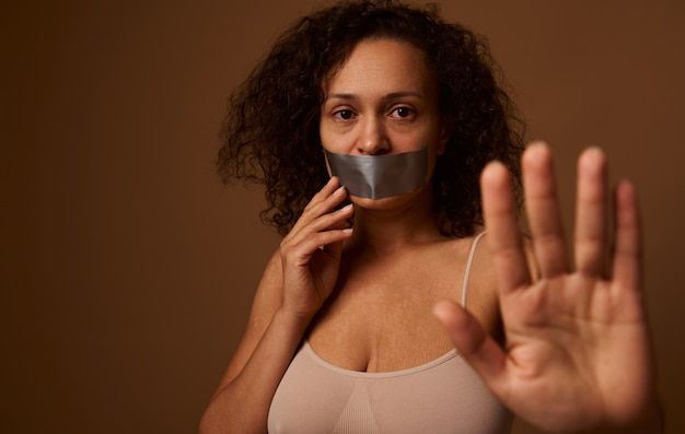 Desperately scared crying woman with tears in her eyes, sealed mouth shows stop sign with hand looks at camera, isolated on dark beige background. social concept of elimination violence against women