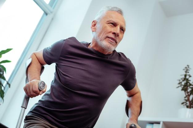 困難にもかかわらず。松葉杖で歩こうとしている間、彼の前を見て強い老人