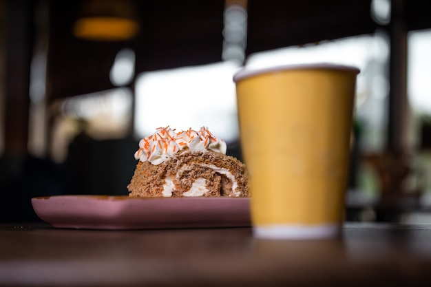 Десерт и чашка кофе на деревянном столе в кафе.