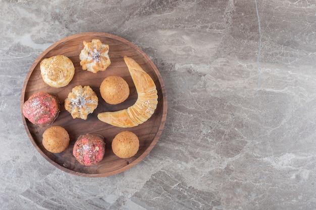 Десертное ассорти с печеньем, булочками и кексами на подносе на мраморной поверхности