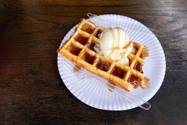 木製の背景にキャラメルシロップを注いだクリーミーなアイスクリームのボールとデザートベルギーワッフル