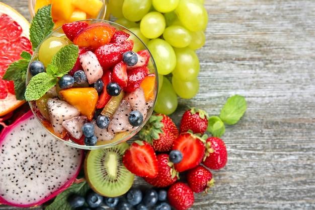 Десертная чаша с вкусным фруктовым салатом на деревянном столе