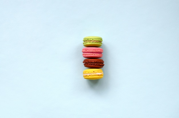 Dessert cake macaron or macaroon on trendy pastel blue background top view.