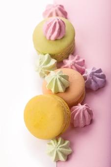 분홍색 배경 평면도에 디저트 케이크 마카롱 또는 마카롱.