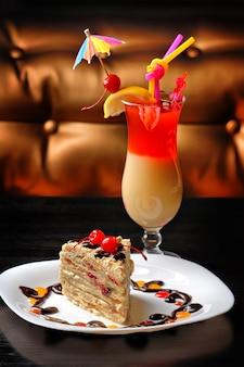 Десертный торт на тарелке украшенный вишней на коктейльном столе
